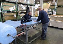Zwei Mitarbeiter beim Verpacken von Fertigungsteilen - Verpackungs- und Logistikdienstleister ad laborem gGmbH